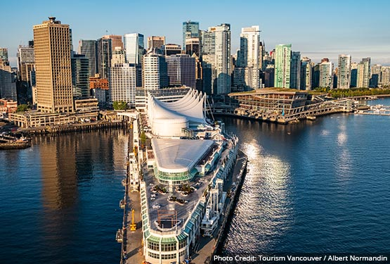 An aerial view of downtown Vancouver with the white sails of Canada Place on a pier.