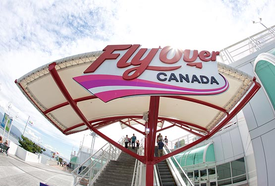 A view up stairs past a large FlyOver Canada sign and awning