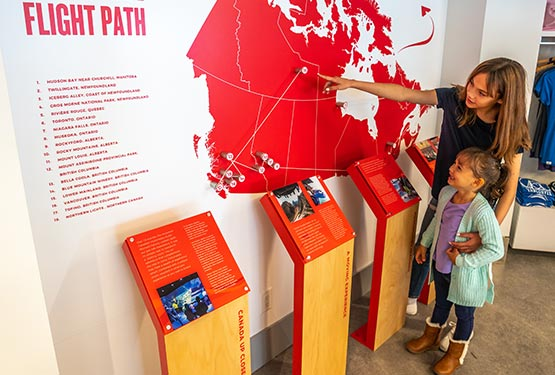 A mom and kid look at a map of Canada on a wall.