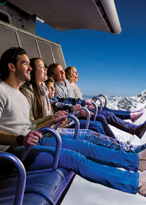 A group of people smile while riding a flight ride in front of a large film screen.