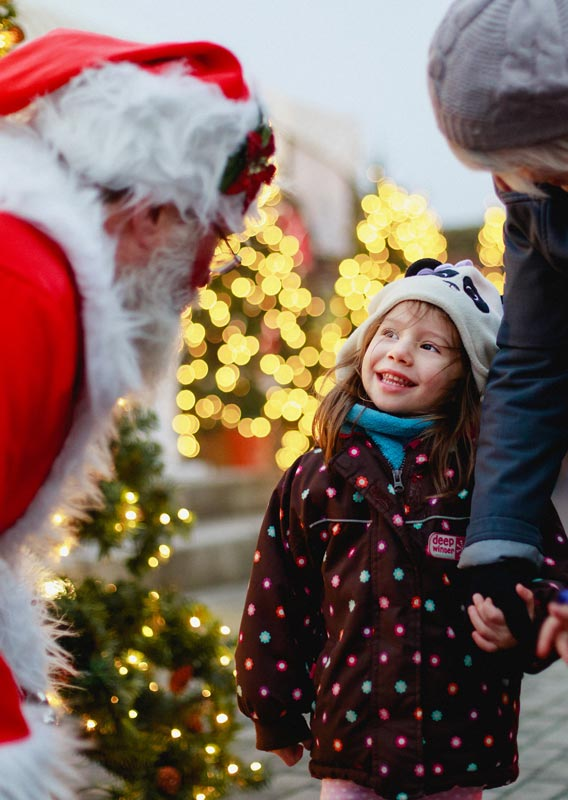 Two children meet Santa Claus at a Christmas Market