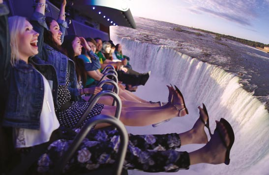 People smile in excitement on the FlyOver Canada flight-ride as big screens show Niagara Falls