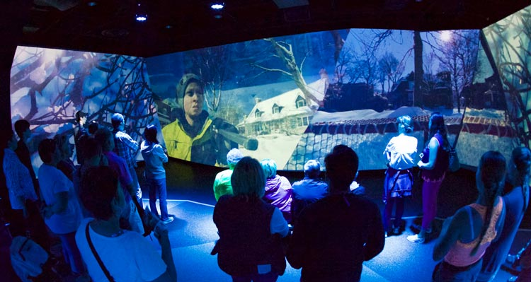 A crowd of people watch an immersive video experience