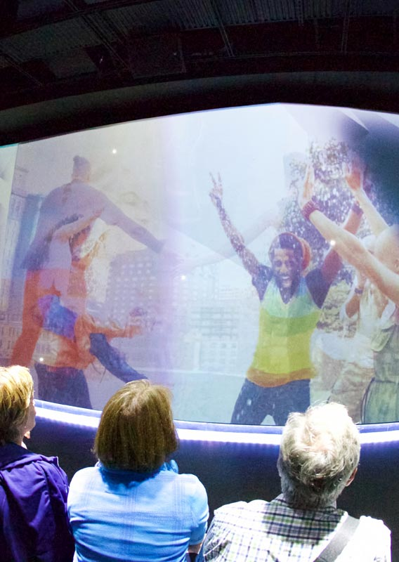 A crowd watches the UpLift experience with dancers on screen.