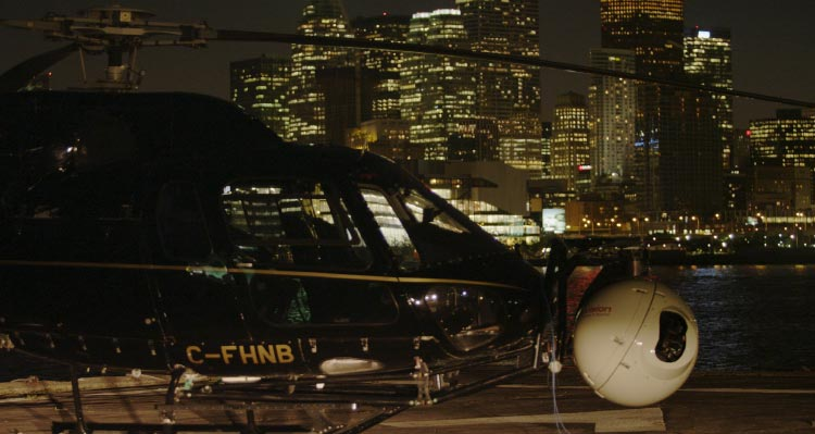 A helicopter with a video camera attached gets ready to take off with skyscrapers behind.