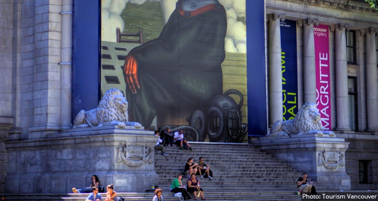 People sit on the steps of the Vancouver Art Gallery, between two lion statues.