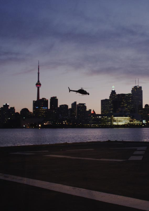 A helicopter flies over water between a helipad and the Toronto skyline at dusk.