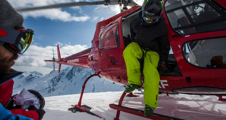 A skiier gets out of a red helicopter.