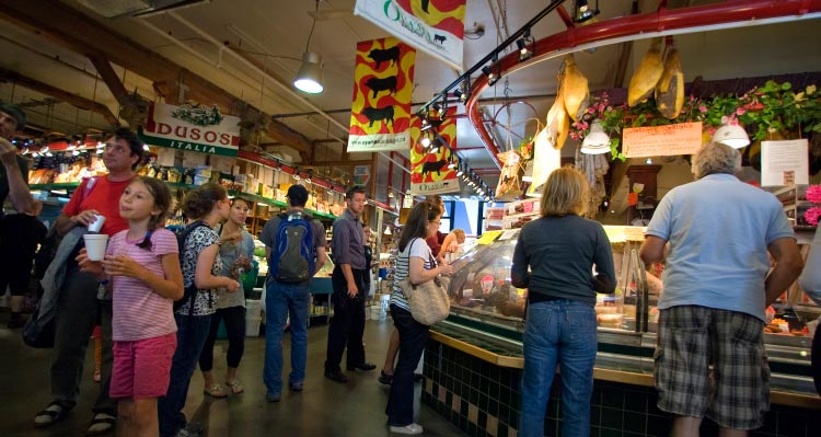 Crowds fill an indoor market to shop for meats.