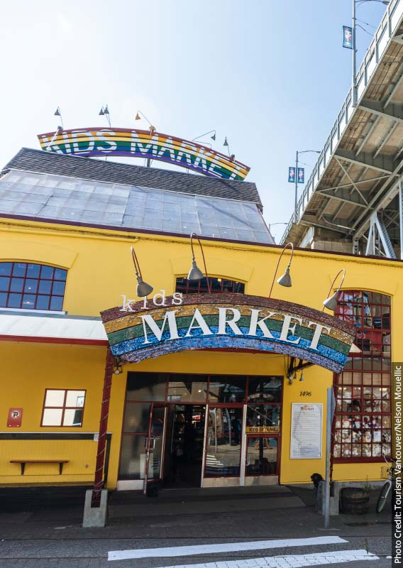 A yellow market building decorated with rainbows sits below a steel bridge.