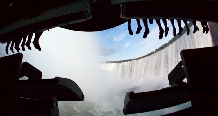 Visitors' feet dangle from the FlyOver Canada flight-ride, while Niagara Falls is shown on the screen.