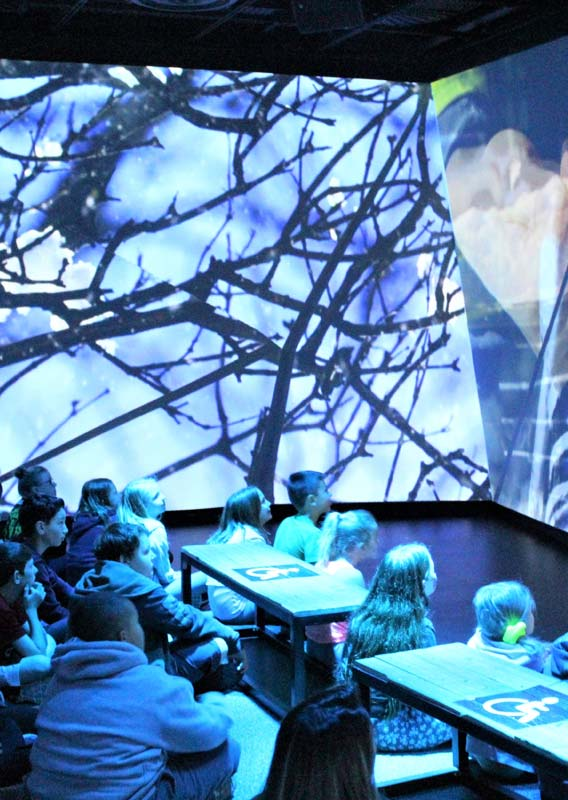A group of children stand sit, watching a large projected video screen.