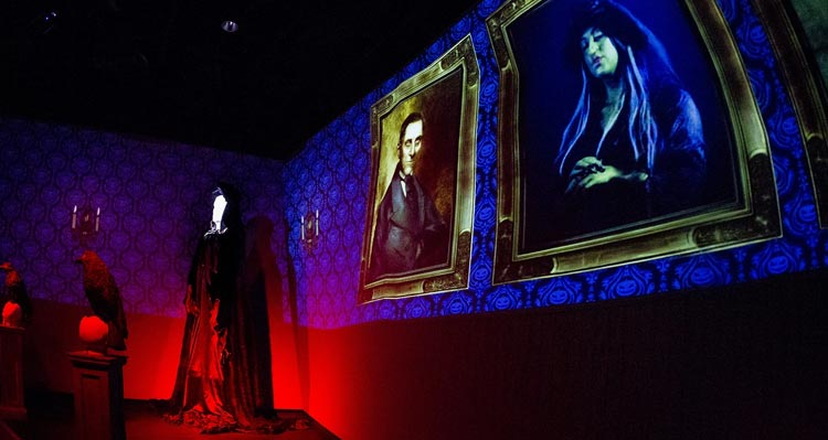 A projection of spooky portraits in a Halloween-decorated room.