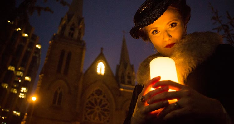 A woman holds a candle in front of a gothic cathedral at night time.