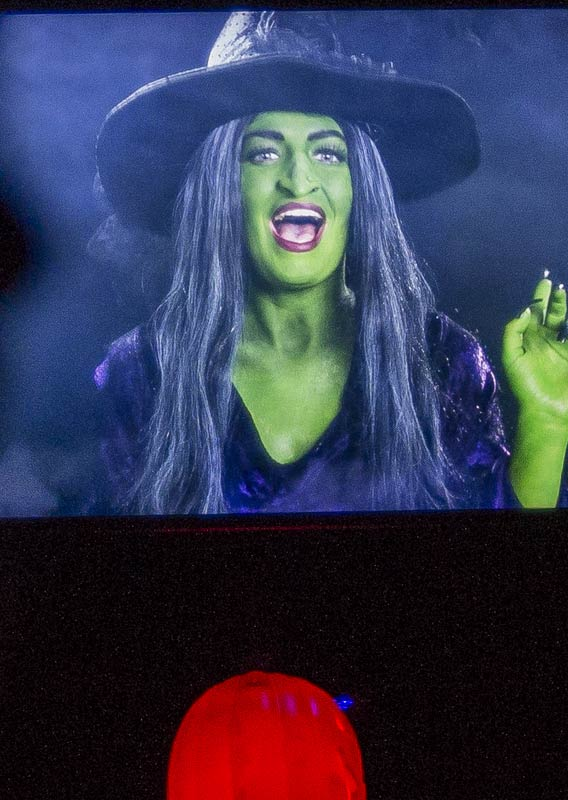 A witch with green skin on a projected screen.