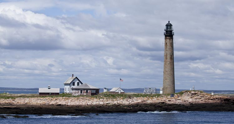 An historic lighthouse stands a the seashore near some buildings.