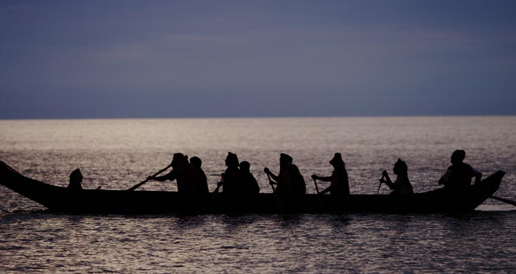 A group of people canoe on the open ocean.