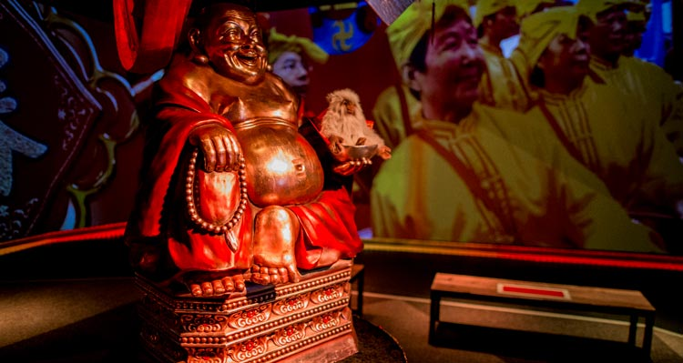 The Flight of the Dragon pre-show area, showing video and a Buddha statue