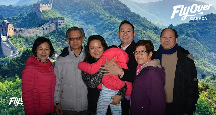 A family photo in front of a Great Wall of China backdrop