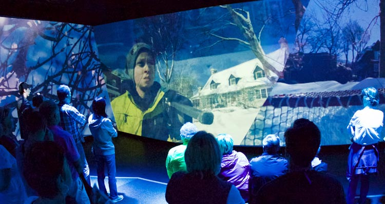 A group of people watch a cinematic presentation showing Canadian life.