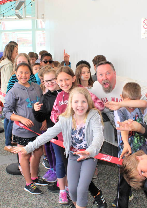 A group of smiling children in the line for FlyOver Canada