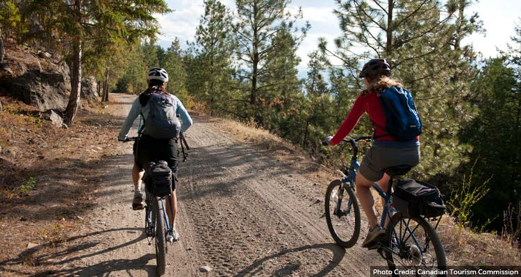 Two mountain bikers ride on a dirt pathway along a forested hillside.