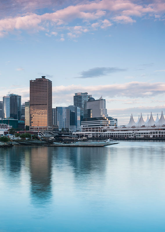 Vancouver skyline over water with high rise buildings and pink clouds