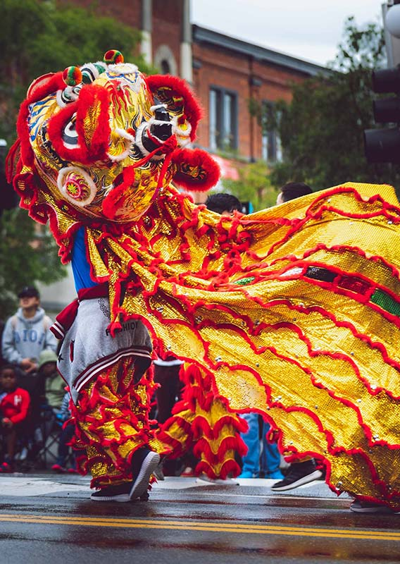 A dancer costumed for a lion dance on a street for a parade.